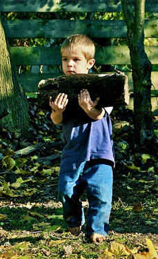 Young boy helps carry fire wood